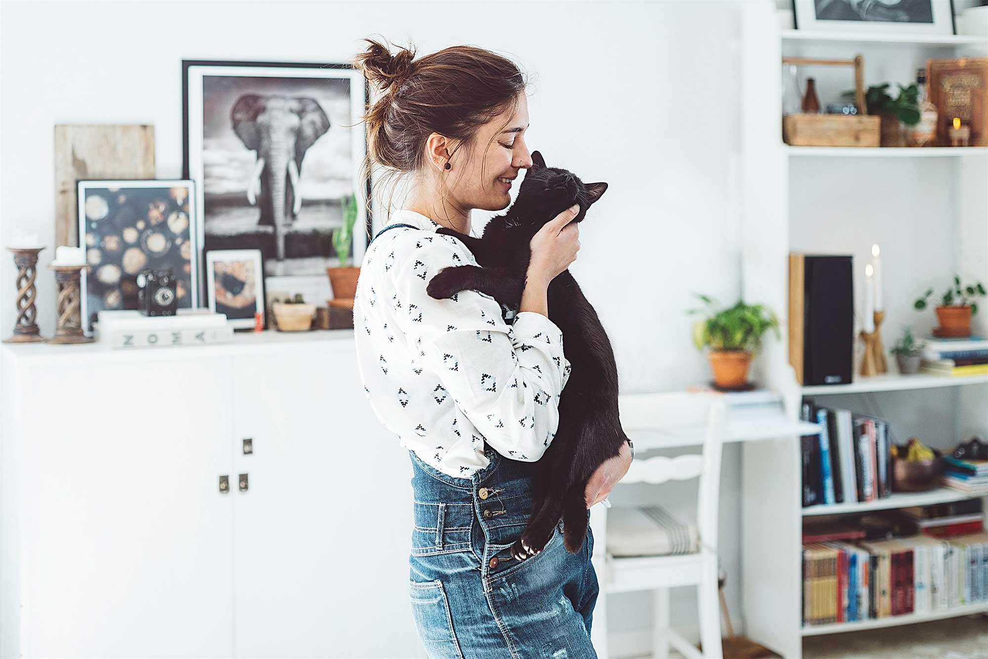 Person i ett rum som kramar en svart katt