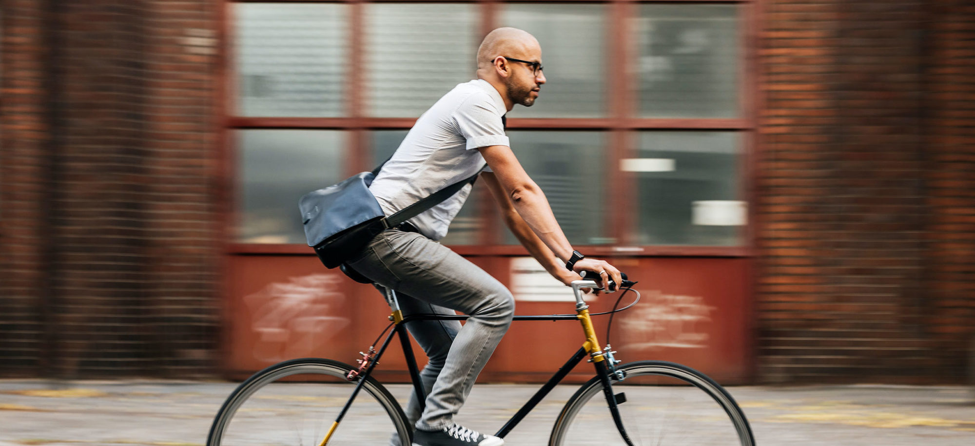 Person cyklar framför en tegelbyggnad