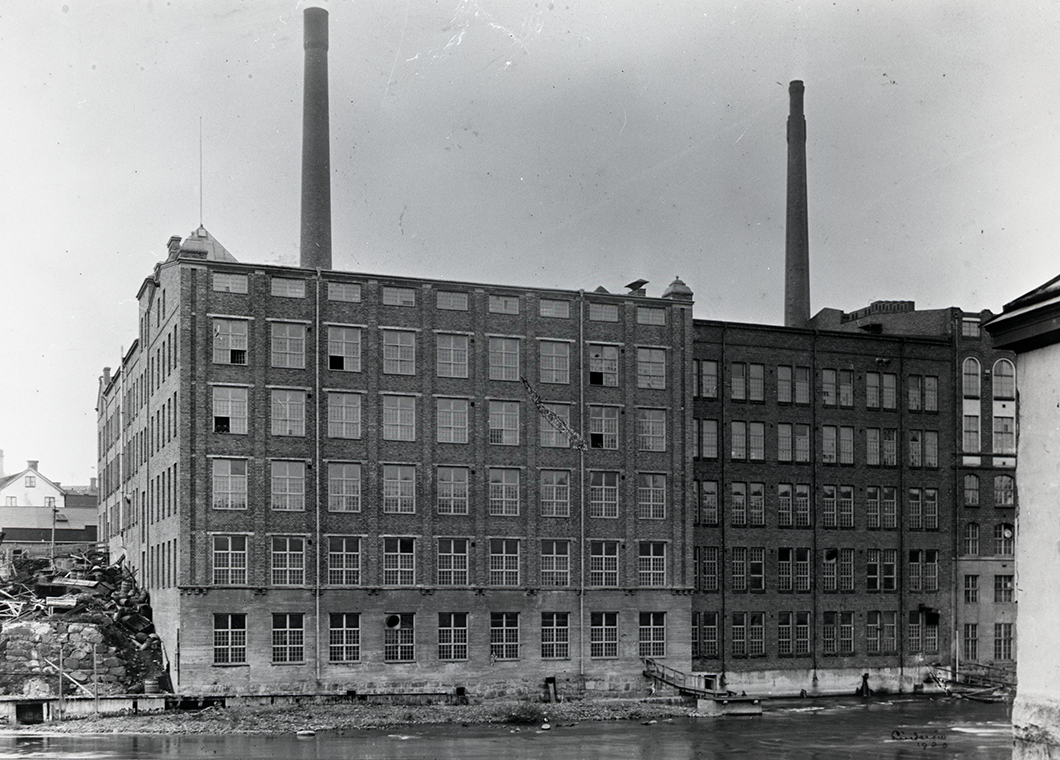 Gammal svartvit bild på yllefabriken. En tegelbyggnad med höga skorstenar och många fönster precis vid Strömmen